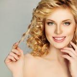 Белокурая девушка вьющиеся волосы Красивая усмехаясь женщина касается ее волосам Стоковые Фото