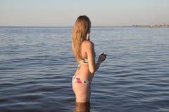 Белокурая девушка в бикини стоя в морской воде Красивая молодая женщина в красочном бикини на предпосылке моря Стоковые Изображения