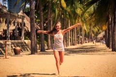 белокурая девушка в шнурке бежит barefoot между ладонями на пляже Стоковое фото RF