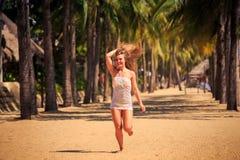белокурая девушка в шнурке бежит barefoot между ладонями на пляже Стоковые Фотографии RF