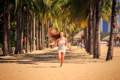 белокурая девушка в шнурке бежит barefoot между ладонями на пляже Стоковое Фото