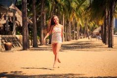 белокурая девушка в шнурке бежит barefoot между ладонями на пляже Стоковая Фотография