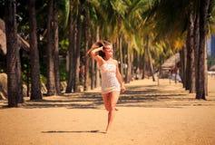 белокурая девушка в шнурке бежит barefoot между ладонями на пляже Стоковое Изображение