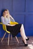 Белокурая девушка в юбке и жилете сидит на стуле Стоковое Изображение