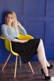 Белокурая девушка в юбке и жилете сидит на стуле Стоковые Фотографии RF