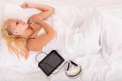 Белокурая девушка лежа в кровати с ПК таблетки Стоковое Изображение RF