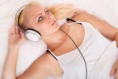 Белокурая девушка лежа в кровати слушая к музыке Стоковые Изображения RF