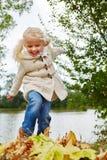 Белокурая девушка играя с листьями Стоковая Фотография RF