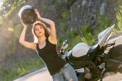 Белокурая девушка извлекает его шлем около мотоцикла стоковое фото