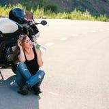 Белокурая девушка извлекает его шлем около мотоцикла стоковое фото rf