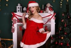 Белокурая девушка носит костюм Санты, представляющ около рождественской елки и печной трубы Стоковые Изображения RF