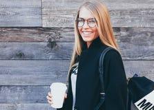 Белокурая девушка нося черное пальто, стекла битника и кофе взятия рюкзака выпивая отсутствующий в бумажном стаканчике стоя проти Стоковые Изображения RF