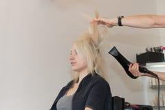 Белокурая девушка получая дуновение волос высушенный Стоковые Изображения