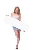 Белокурая девушка представляя при большой nameplate изолированный на белой предпосылке стоковое изображение rf