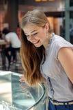 Белокурая девушка рассматривает ювелирные изделия в магазине Стоковые Изображения