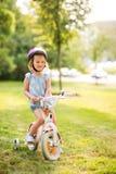 Белокурая девушка сидит на ее велосипеде в парке города Стоковое Изображение