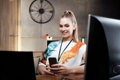 Белокурая девушка сидя на столе используя мобильный телефон Стоковые Фото