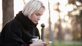 Белокурая девушка снаружи в руках smartphone и кофе уныло читая сообщение на smartphone видеоматериал