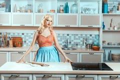 Белокурая девушка стоя в кухне рядом с плитой Стоковая Фотография