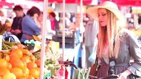 Белокурая девушка с велосипедом идет на рынок, пахнуть апельсином сток-видео