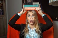 Белокурая девушка с книгами на ее голове Стоковые Изображения RF