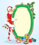 Белокурая девушка xmas нося костюм Санта Клауса оставаясь рядом с рамкой Стоковая Фотография