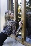 Белокурая женщина в животной склонности рубашки печати против витрины Стоковые Фото