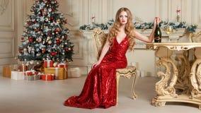 Белокурая женщина в красном платье с стеклом белого вина или шампанского распологая на стул в роскошном интерьере рождество моя в Стоковое фото RF