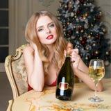 Белокурая женщина в красном платье с стеклом белого вина или шампанского распологая на стул в роскошном интерьере Рождественская  Стоковые Фото