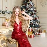 Белокурая женщина в красном платье с стеклом белого вина или шампанского распологая на стул в роскошном интерьере рождество моя в Стоковые Фото