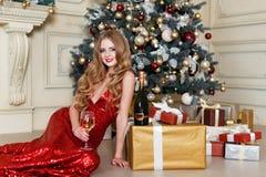 Белокурая женщина в красном платье с стеклом белого вина или шампанского в роскошном интерьере Рождественская елка, настоящие мом Стоковое Фото