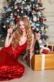 Белокурая женщина в красном платье с стеклом белого вина или шампанского в роскошном интерьере Рождественская елка, настоящие мом Стоковые Изображения RF