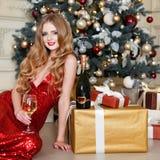Белокурая женщина в красном платье с стеклом белого вина или шампанского в роскошном интерьере Рождественская елка, настоящие мом Стоковые Фото