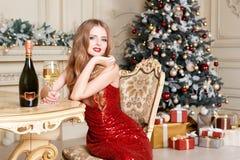 Белокурая женщина в красном платье с стеклом белого вина или шампанского распологая на стул в роскошном интерьере рождество моя в Стоковая Фотография