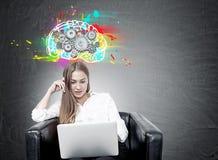 Белокурая женщина в кресле, компьтер-книжке, cogs мозга стоковая фотография rf