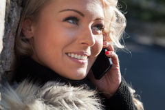 Белокурая женщина говоря на ее усмехаться мобильного телефона Стоковое Изображение