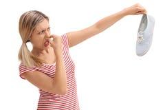 Белокурая женщина держа вонючий ботинок Стоковое Фото