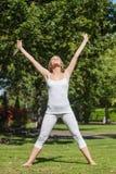 Белокурая женщина делая йогу в парке Стоковые Изображения RF
