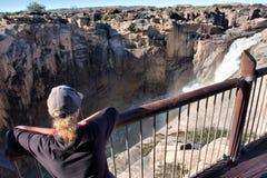 Белокурая женщина наблюдая огромный водопад стоковые фото