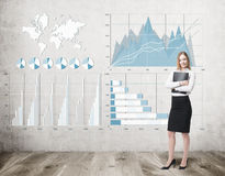 Белокурая женщина обнимая папку около бетонной стены с диаграммами Стоковые Фотографии RF