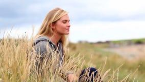 Белокурая женщина ослабляя в дюнах акции видеоматериалы