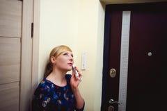 Белокурая женщина отвечает звонку внутренной связи, держит телефон к его уху Стоковое фото RF