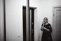 Белокурая женщина отвечает звонку внутренной связи, держит телефон к его уху Стоковое Фото