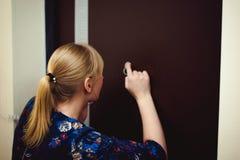 Белокурая женщина отвечает звонку внутренной связи, держит телефон к его уху Стоковое Изображение RF