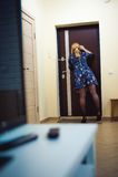 Белокурая женщина отвечает звонку внутренной связи, держит телефон к его уху Стоковая Фотография RF