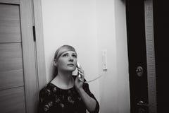 Белокурая женщина отвечает звонку внутренной связи, держит телефон к его уху Стоковая Фотография