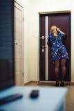Белокурая женщина отвечает звонку внутренной связи, держит телефон к его уху Стоковые Фото