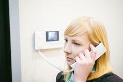 Белокурая женщина отвечает звонку внутренной связи Стоковое Изображение RF