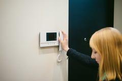 Белокурая женщина отвечает звонку внутренной связи Стоковые Изображения RF