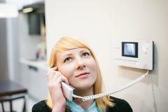 Белокурая женщина отвечает звонку внутренной связи Стоковая Фотография RF